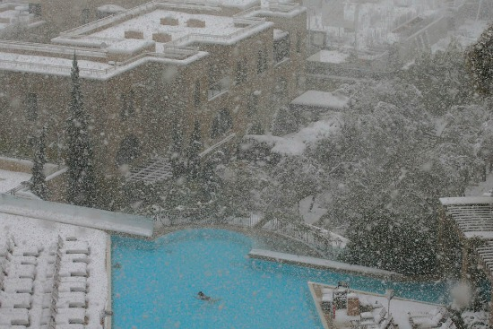 Swimmer in hotel pool while snowing