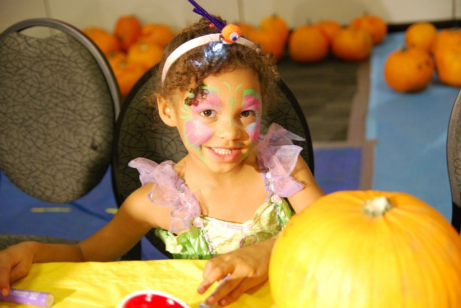 girl dressed as a fairy decorating pumpkin