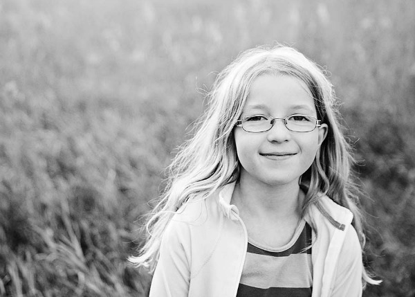Girl standing in field wearing glasses