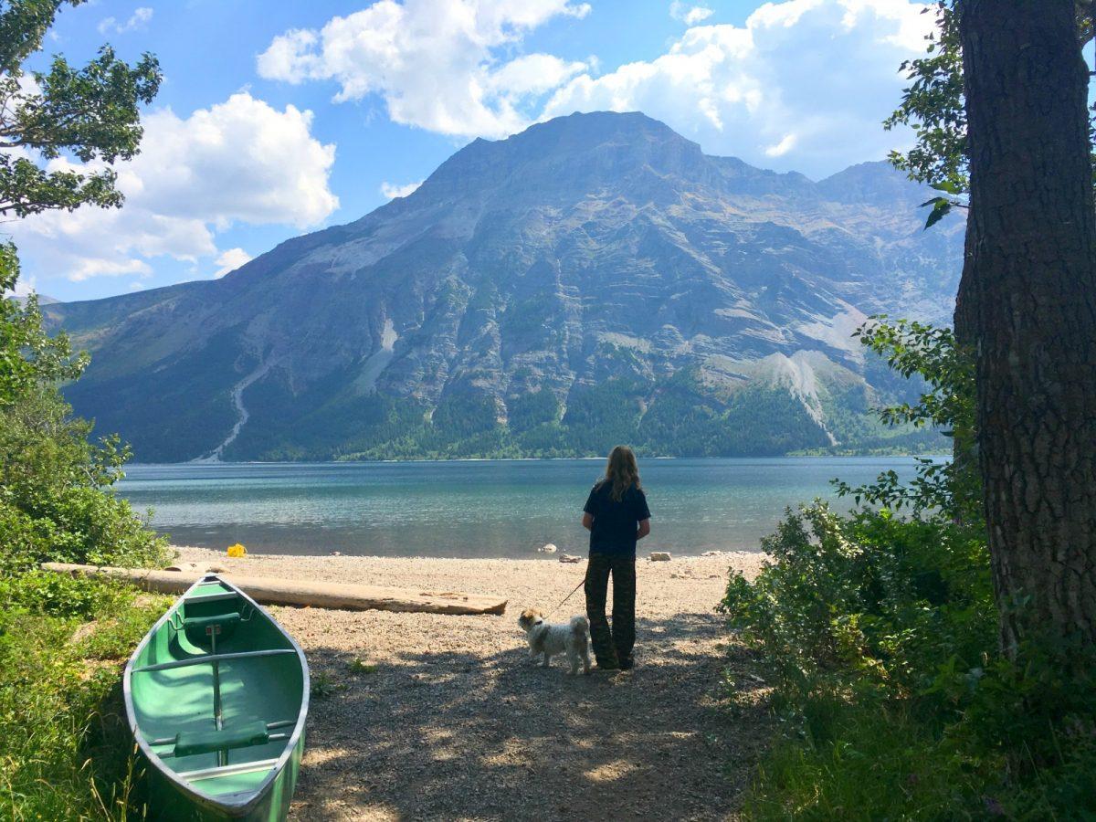 girl walking dog by mountain lake